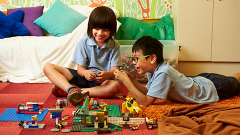 two boys playing with Lego